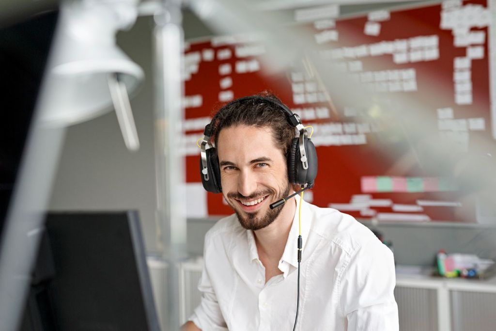 Artificial intelligence in the call center. Call center agent smiling at his workstation.